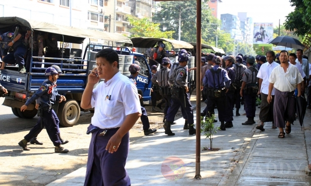 A Myanmar police  man talks with a farmer protester during a rally against the government in downtown Yangon Thursday, Oct.27, 2011, in Yangon, Myanmar