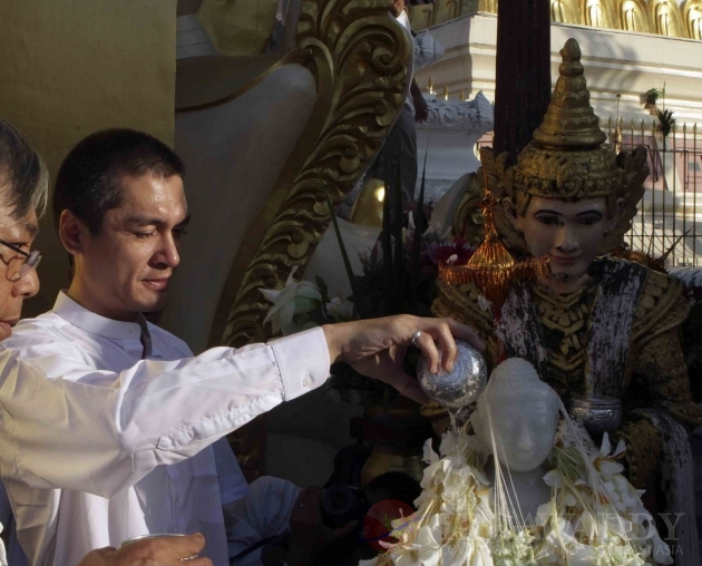 Aung San Suu Kyi's son Kim Aris pour water on the white Buddha status at the famous Shwedagon pagoda in Rangoon, Burma.