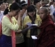 The leader of National League for Democracy (NLD) Aung San Suu Kyi gives alms to monks in Rangoon, Burma.