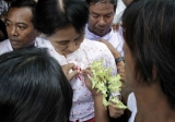 Burma pro-democracy leader Aung San Suu Kyi receives flowers from the local people.