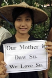 """A woman shows the letters """"Our mother is Daw Su. We Love Su"""", during pro-democracy Aung San Suu Kyi visit at the community-dwelling."""