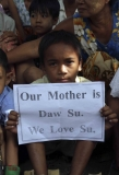 """A boy shows the letters """"Our mother is Daw Su. We Love Su"""", during pro-democracy Aung San Suu Kyi visit at the community-dwelling."""