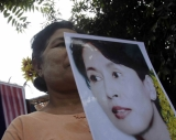 A woman hold a Aung San Suu Kyi's portrait to welcome National League for Democracy leader Aung San Suu Kyi at the NLD headquarters in Rangoon, Burma.