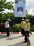 Cleaners clean the road in front of the U Myint Lin's campaign poster, Union Solidarity and Development Party (USDP).