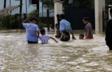 Parents took their children to cross flood.