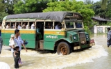 A bus attempts to carry passengers to cross the flood streets in Bago Division, in Burma.
