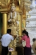 Buddhist devotees pour water to Buddha image as they pay homage to world famous Shwedagon Pagoda in Rangoon, Burma.