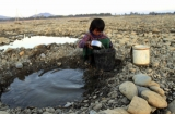 A girl fetches water from a pool in a dry river in Myitkyina, Kachin State, about 1,600 km (1,000 miles) north of Rangoon, Burma.