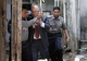 Burma policemen escort Ross Dunkley, founder of the English-Language Myanmar Times, as he leaves Kamayut township court after hearing in Rangoon, Burma. Dunkley has been held in Rangoon's Insein Prison since his February 10 arrest for allegedly overstaying a visa.