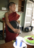 Young novice collecting alms at the coffee shop in Rangoon, Burma.