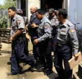 Burma policemen escort Ross Dunkley, founder of the English-Language Myanmar Times, as he leaves Kamayut township court after hearing in Rangoon, Burma. Dunkley has been held in Rangoon's Insein Prison since his Feb. 10 arrest for allegedly overstaying a visa.
