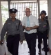 Burma policemen escort Ross Dunkley, founder of the English-Language Myanmar Times, as he leaves Kamayut township court after hearing in Rangoon, Burma.