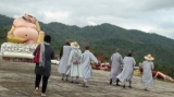 Monks walk past the statue which was destroyed by the earthquake in Tarlay, Easter Shan State, Burma.