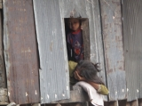 A migrant child look at his mom during she take a nap in Ranong, Thailand.