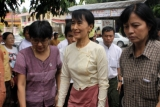 Burma pro-democracy leader Aung San Suu Kyi arrives at her National League for Democracy to attend a ceremony of donation cash to family members of political prisoners at NLD party's headquarters, in Rangoon, Burma.