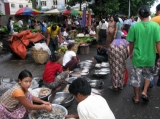 Customer buys fishes from road site stall in downtown in Rangoon, Burma.