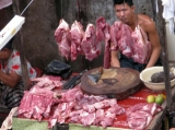 A butcher waits for customers from their road site stall in downtown in Rangoon, Burma.