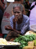A vendor has a smoke as she sells green groceries on a road in downtown in Rangoon, Burma.