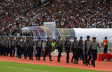 Burmese police officers walk into the field.
