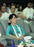Myanmar democracy icon Aung San Suu Kyi, second left, arrives to attend the Conference on Green Economy and Green Growth at Myanmar Banks Association Hall in Yangon, Myanmar, Friday, Nov. 4, 2011. Others in the photo are unidentified.