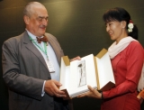Myanmar opposition leader Aung San Suu Kyi, right, receives a posthumous gift from a Foreign minister of Czech Republic, Karel Schwarzenberg, left, during their meeting at Thingaha hotel in Naypyitaw, Myanmar, Tuesday, July 17, 2012.