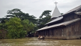 21-08-12 Delta flooding Residents paddle past a Christian church after flooding in the Delta region of Burma