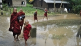 21-08-12 Delta flooding Young Monks wade through water after flooding in the Delta region of Burma