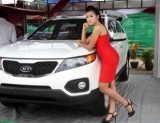06-09-12 luxury car show - PHOTO - Khin Maung Win A model poses with cars displayed at ' The Most Amazing Exhibition and Car Show 2012 ' at Myanmar Convention Centre (MCC) in Yangon, Myanmar.