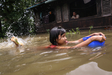 Children swiming on a flooded water in Hlegu at the Yangon region of Myanmar.