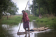 Woman  paddles a makeshift bamboo raft on a flooded water in Hlegu at the Yangon region of Myanmar.
