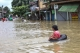 local resident through a flooded road after the Bago River swollen in Bago.