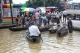 local residents on a boat through a flooded road after the Bago River swollen in Bago.
