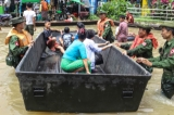 Myanmar military help transport local residents on a rubber boat through a flooded road after the Bago River swollen in Bago.