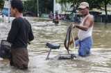 local residents show a dead snake a flooded road after the Bago River swollen in Bago.