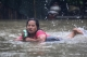 A Woman drinking Heineken while riding on the life-buoy on 6th August despite of houses drowned in certain wards from Bago Region due to the heavy rain and unusual tide.