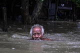 An old man swimming to his destination on 6th August as the houses from some wards in Bago Region were floated due to the heavy rain and unusual tide.