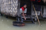 A woman waiting for the boat from her home on 6th August as the houses from some wards in Bago Region were floated due to the heavy rain and unusual tide