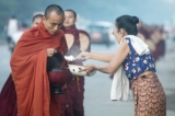 A layperson offering rice to monks
