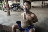 Shwe Pharsi carries a concrete block to strengthen his neck, February 2015. (Photo: Timo Jaworr / The Irrawaddy)