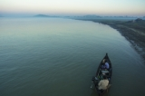 two fishermen coaxing an Irrawaddy dolphin to go fishing with them at dawn. (Photo -teza hlaing/ The Irrawaddy)