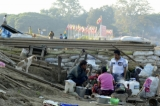 A family having breakfast near a torn-down squatter's house ahead of the arrival of the ship carrying Norwegian King. (Photo - teza hlaing / The Irrawaddy)