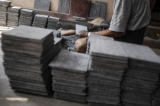 A worker cutting slates to the required size. (Photo: Tin Htet Paing / The Irrawaddy)