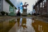 An ethnic Chin man walks past a statue in Siangsawn village. (Photo: Pyay Kyaw / The Irrawaddy)
