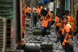 Rangoon's municipal workers cleaning the litter-strewn back alleys of downtown apartments blocks on November 11, 2016. (Photo: Hein Htet/ The Irrawaddy)