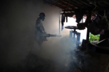 A man fumigates a house in Rangoon to kill mosquitoes carrying diseases. Hein Htet/ The Irrawaddy